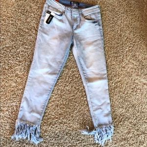 Light wash jeans with fringed ankles